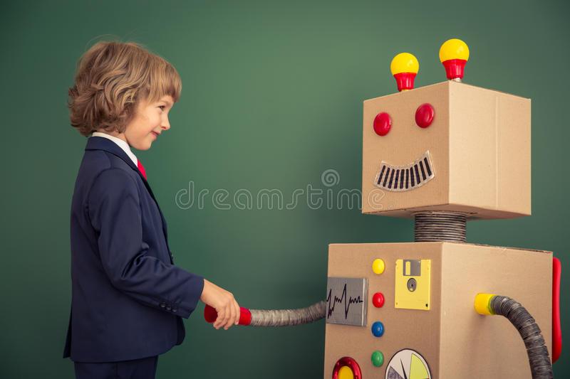 Kid with toy robot in school. Success and innovation technology concept stock photo