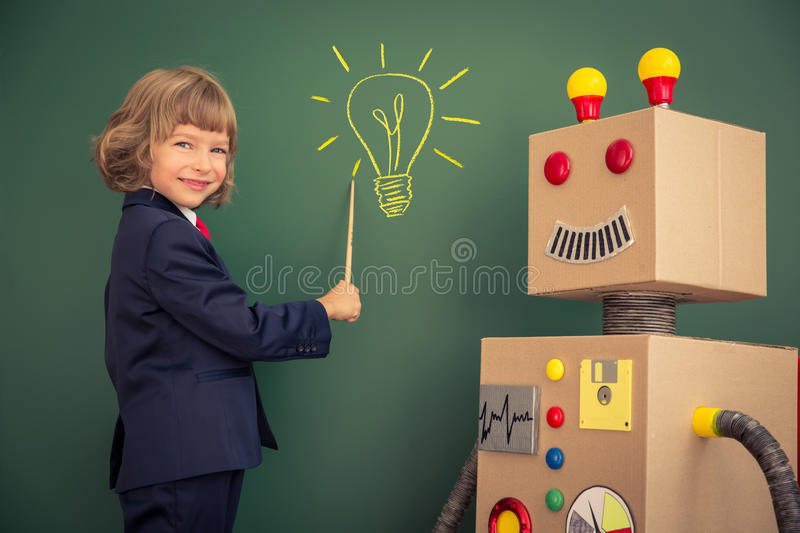 Kid with toy robot in school. Success and innovation technology concept royalty free stock photography