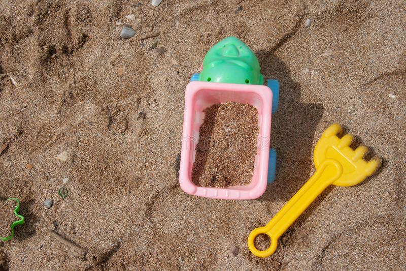 Bright plastic children`s toys in the sand. Concept of beach recreation for children. royalty free stock photos