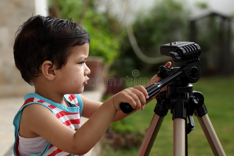 Kid trying his hands on a tripod stock images