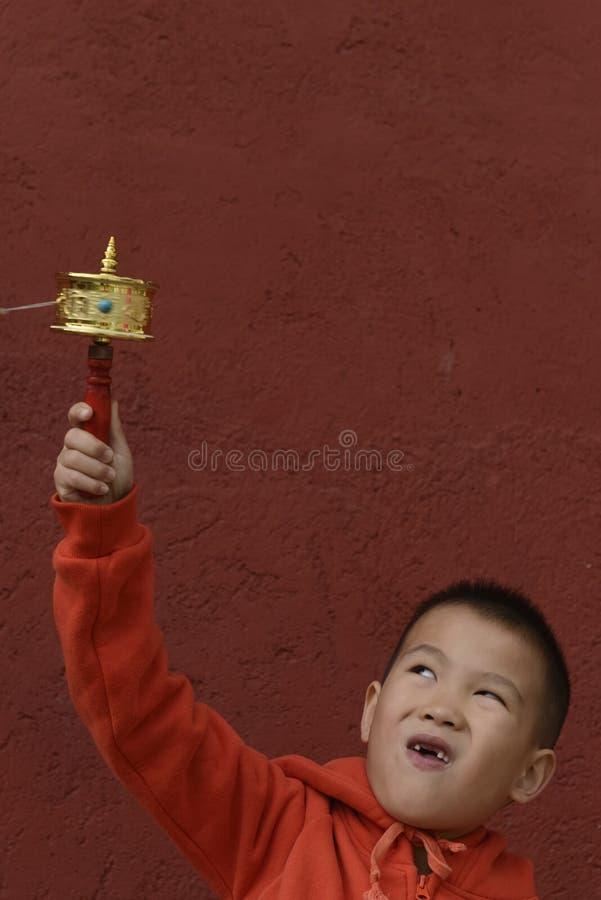 Kid turning prayer wheel. Chinese kid turning prayer wheel with red wall background royalty free stock photos