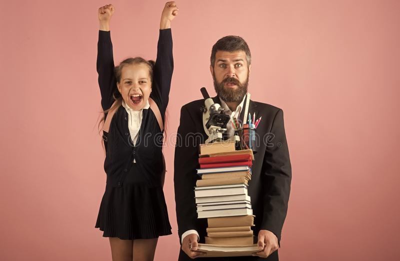 Kid and tutor hold huge pile of books. Education stock image
