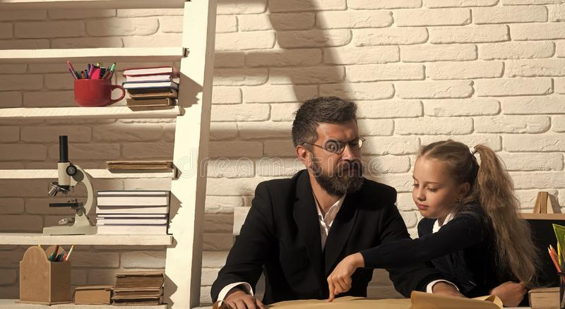Kid and tutor with strict and interested faces royalty free stock image