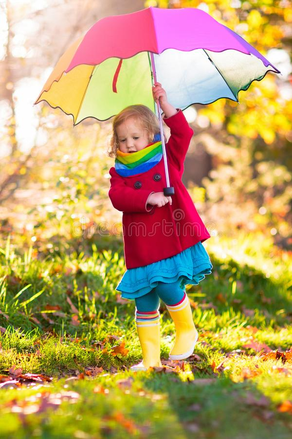 Kid with umbrella playing in autumn rain stock photos