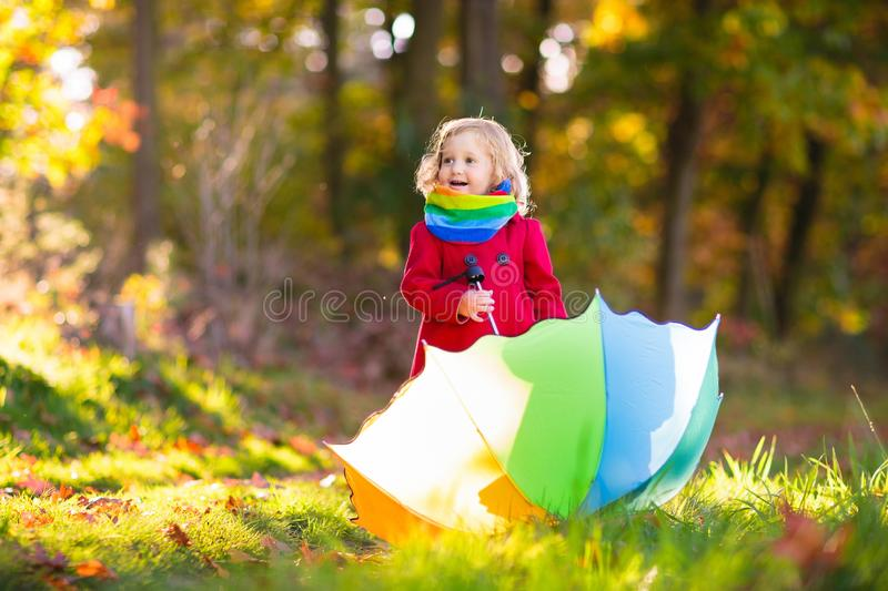 Kid with umbrella playing in autumn rain stock photography