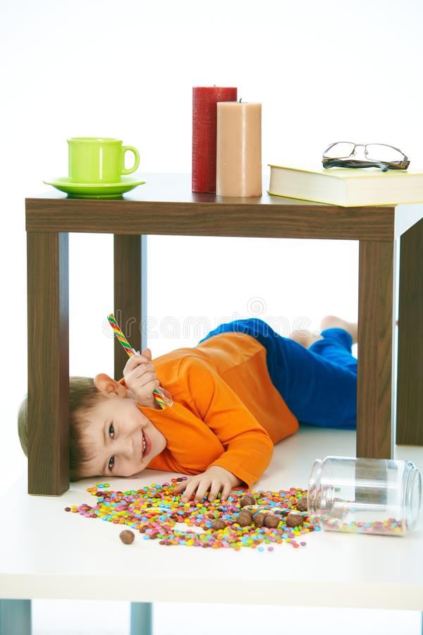 Kid under table with lollipop and sweets jar spilt. Cute caucasian kid lying under table with sweets jar spilt. Happy, smiling, isolated on white, lollipop in royalty free stock images
