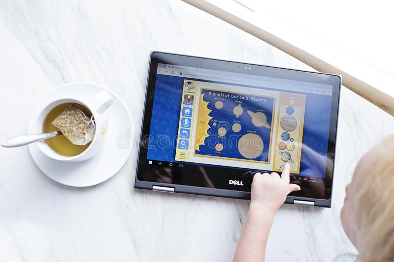 Kid Using Black Dell Tablet With Tea royalty free stock images