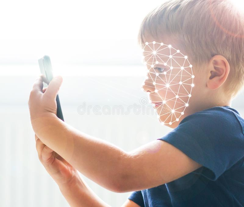 Kid using face id recognition. Boy with a smartphone gadget. Digital native children concept. stock images