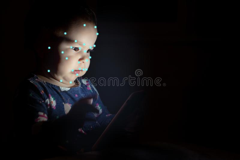 Kid using face id recognition. Boy with a smartphone gadget. Digital native children concept. stock photography