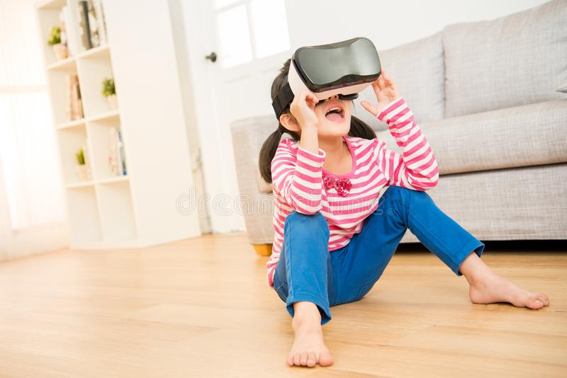 Kid using a virtual reality goggles shocked. Lifestyle shot of an amazed little kid using a virtual reality goggles with mouth open shocked seated on wooden royalty free stock images
