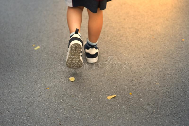 Kid Walking ahead to sun flare on road with fall dry leaves royalty free stock images