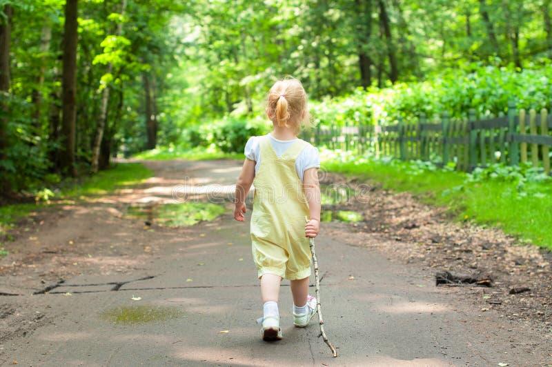 Kid walking. Little blonde kid girl walking in park royalty free stock images