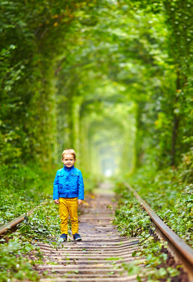 Download Kid Walking The Rails In Green Tunnel Stock Photos - Image: 34120163