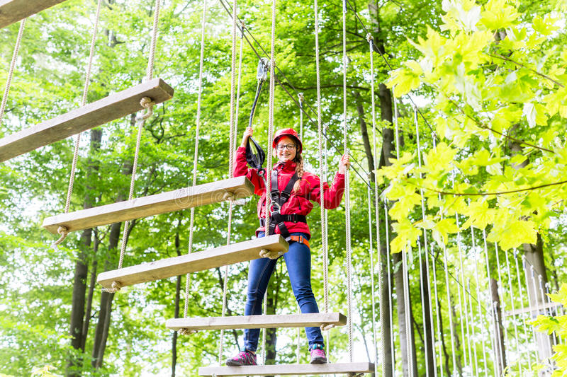 Kid walking on rope bridge in climbing course. Teenage girl, walking on rope bridge in climbing course enjoying the trill of the sport stock photo