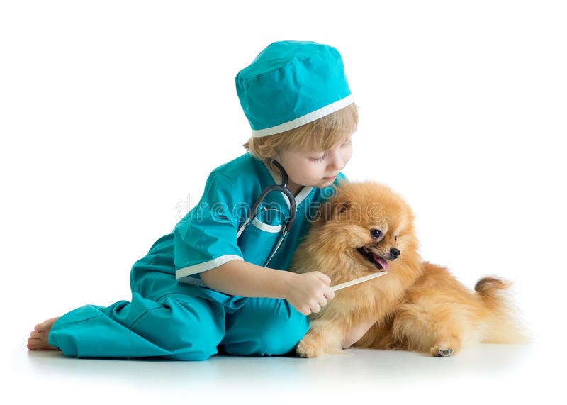 Kid weared doctor clothes playing veterinarian stock photos