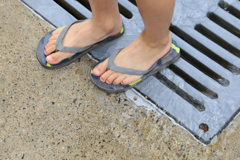 A kid wearing beach flip flops. Children love to play in the water park and flip-flop sandals are the perfect shoe for outdoor fun at the beach or water-park stock photos