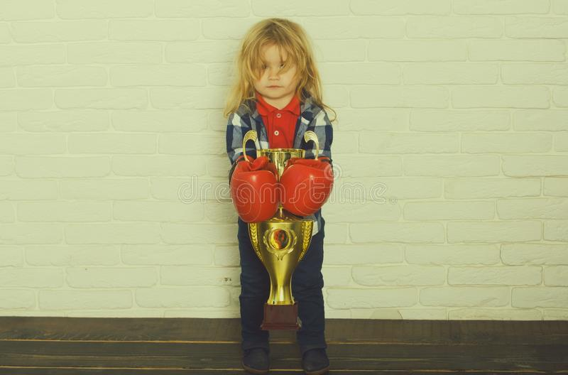 Kid wearing boxing glove, boy boxer winning golden champion cup stock photo