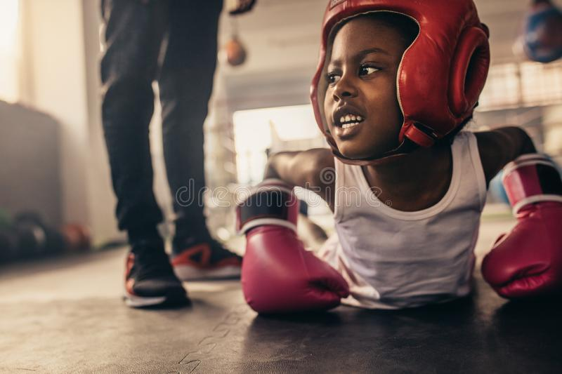 Boxing kid doing push ups on the floor at a boxing gym. Kid wearing boxing gloves and headgear doing push ups. Kid doing warm up exercises before starting his stock images
