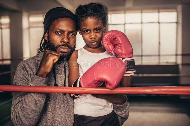 Coach with a boxer kid standing near a boxing ring stock image