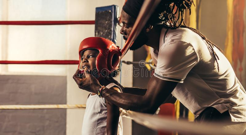 Kid wearing boxing head guard standing inside a boxing ring. Coach fixing a teeth guard to a boxing kid before a fight. Kid getting ready for a fight standing stock photo
