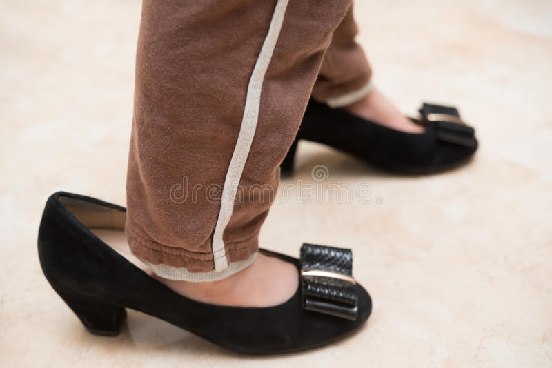 Kid wearing mums trendy shoes for fu. N at home stock photography