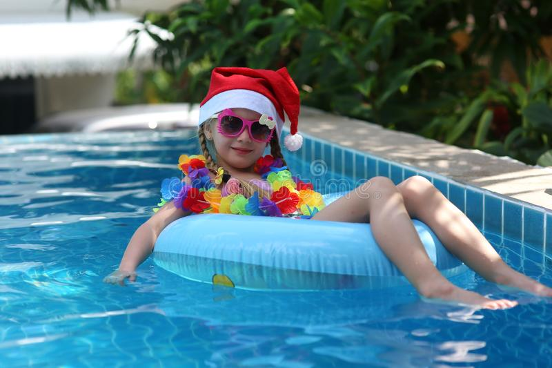Kid wearing Santa Claus hat are swimming in a blue pool on a bright sunny day and smiling. Concept of happy new year and christmas royalty free stock photography