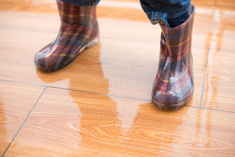 Kid wearing waterproof gumboots standing on wet floor royalty free stock photos