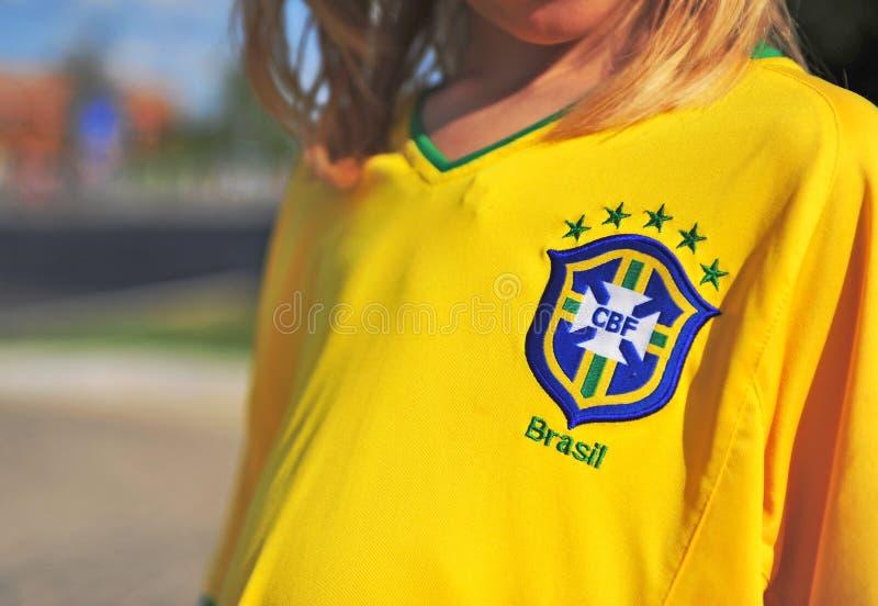 Kid wearing football shirt of Brasil national team. Kid wearing yellow football shirt of Brasil national team stock image