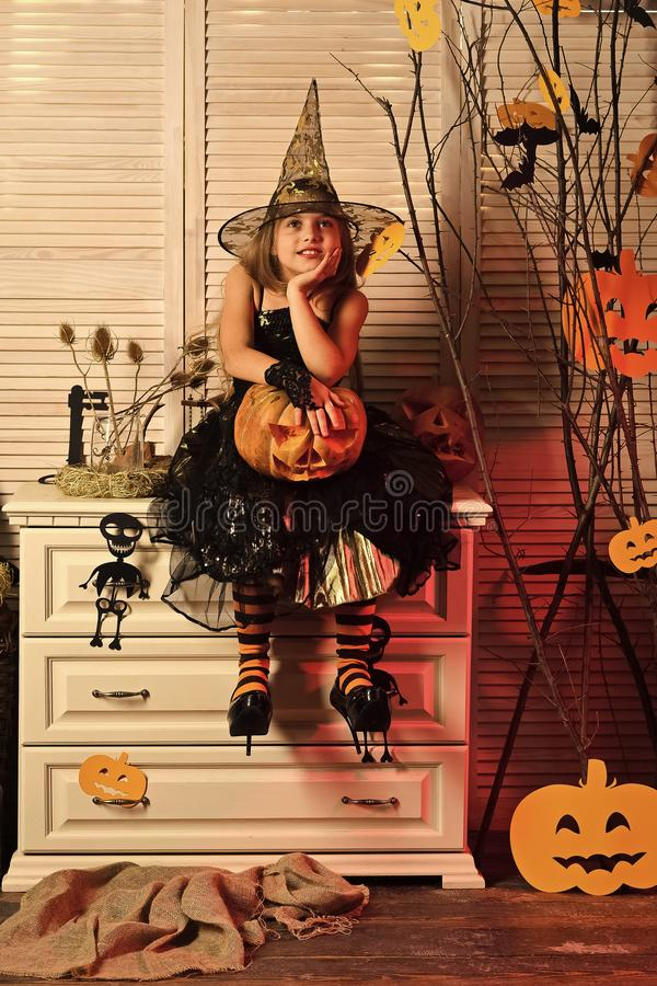 Kid in witch hat and costume holds jack o lantern. Kid in witch hat and costume holds big jack o lantern. Girl with dreamy face on spooky carnival room stock photos