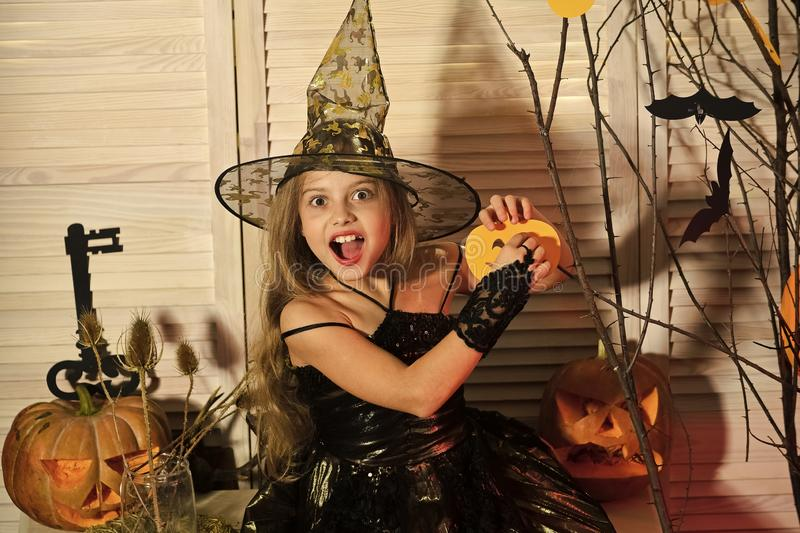 Kid in witch hat and costume holds jack o lantern. Kid in witch hat and costume holds paper jack o lantern. Girl with cheerful face on spooky carnival room stock images