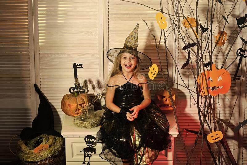 Kid in witch hat and costume sits near scary branches. With decorations. Girl with smiling face on spooky carnival room background. Halloween party and fest royalty free stock images