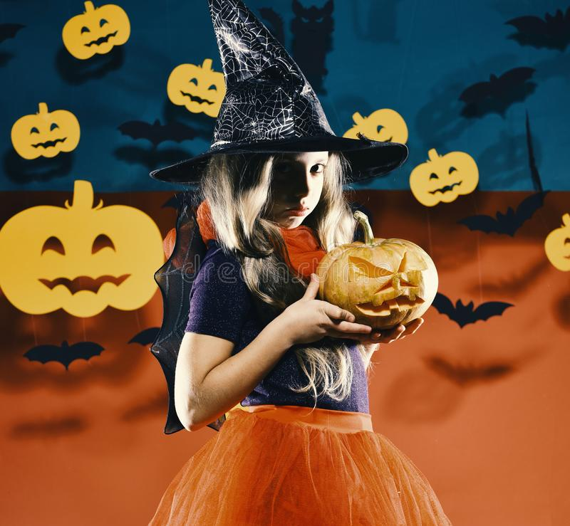 Kid in witch princess costume holds jack o lantern. Little witch wearing black hat. Halloween party concept royalty free stock photography