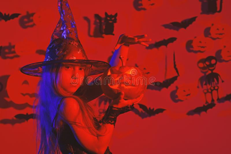 Kid in witches costume holds jack lantern and puts spell. royalty free stock images