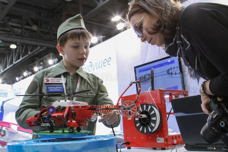 Kid and woman with RC helicopter, focus on the helicopter. Moscow - May 26, 2018: Kid and woman with RC helicopter, focus on the helicopter at the international royalty free stock photos