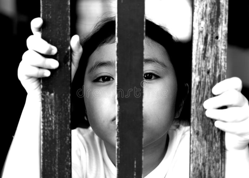 Kid with wood fence, feeling no freedom, black and white photography. Kid with wood fence, feeling no freedom, black and white photography stock images
