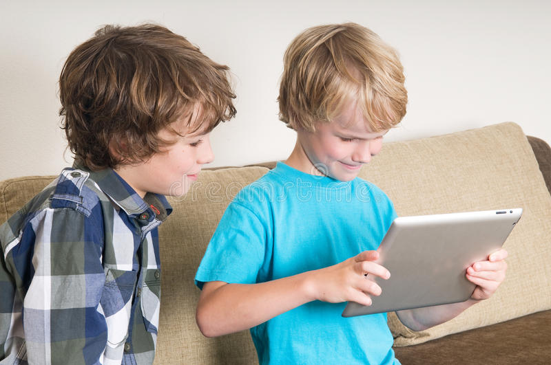 Kid working on a tablet computer. Kid is working on a tablet computer while his brother is watching royalty free stock image