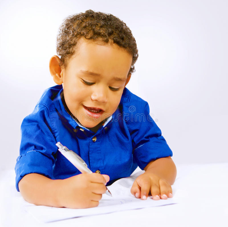 Kid writing. Cute kid writing or doodling with pen on paper royalty free stock images