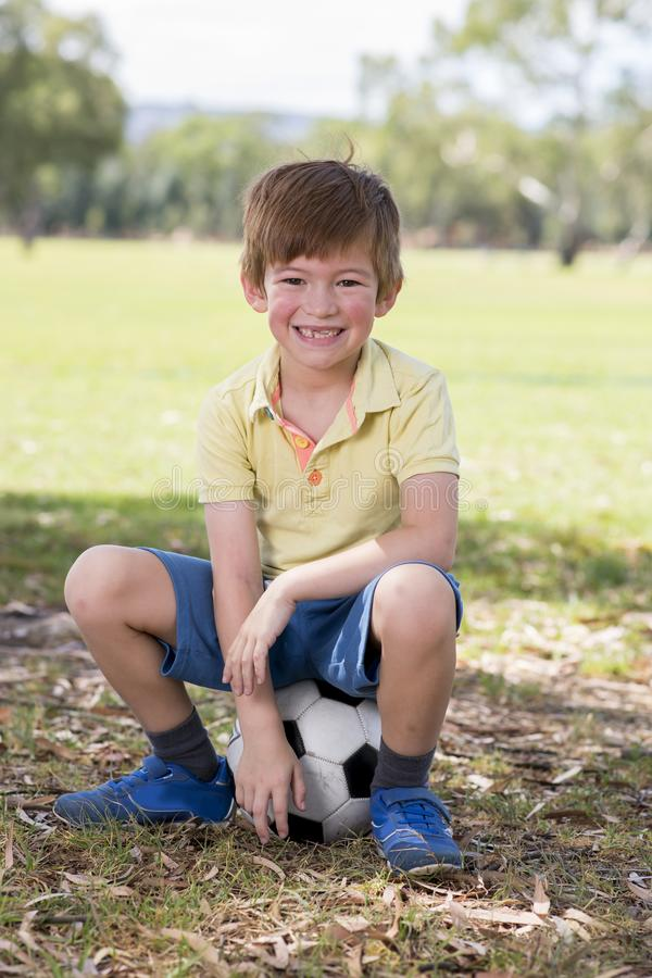 Kid 7 or 8 years old enjoying happy playing football soccer at grass city park field posing smiling proud sitting on the ball in. Young little kid 7 or 8 years royalty free stock image