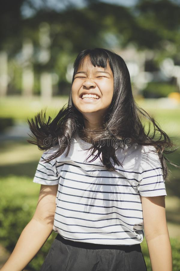 Kidding face of asian teenager showns forelock hair flowing by w royalty free stock images