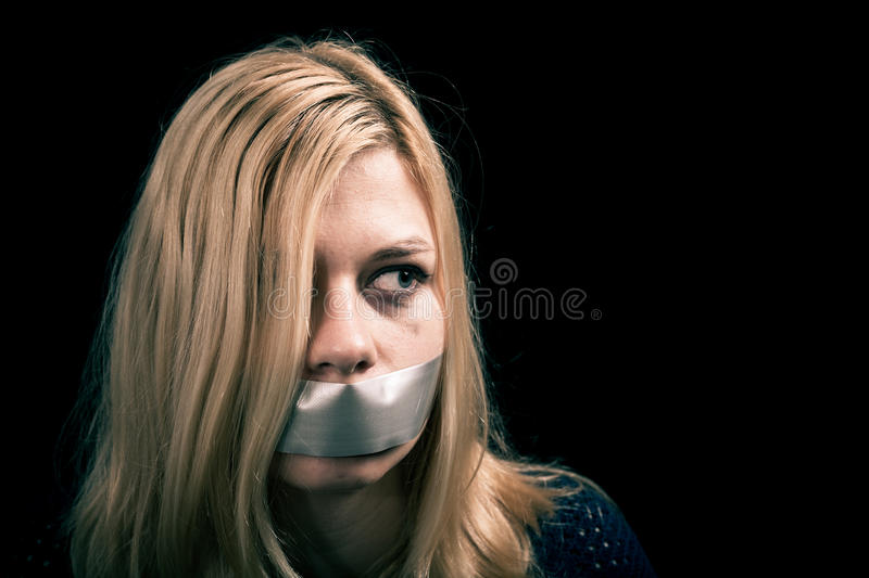Kidnapped woman hostage with tape over her mouth royalty free stock images