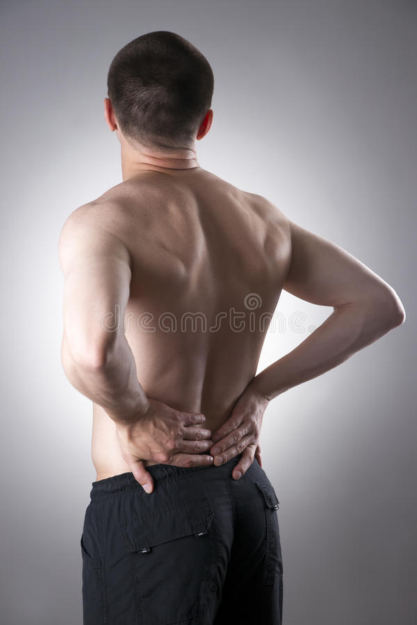 Kidney pain. Man with backache. Pain in the man's body. On a gray background royalty free stock images