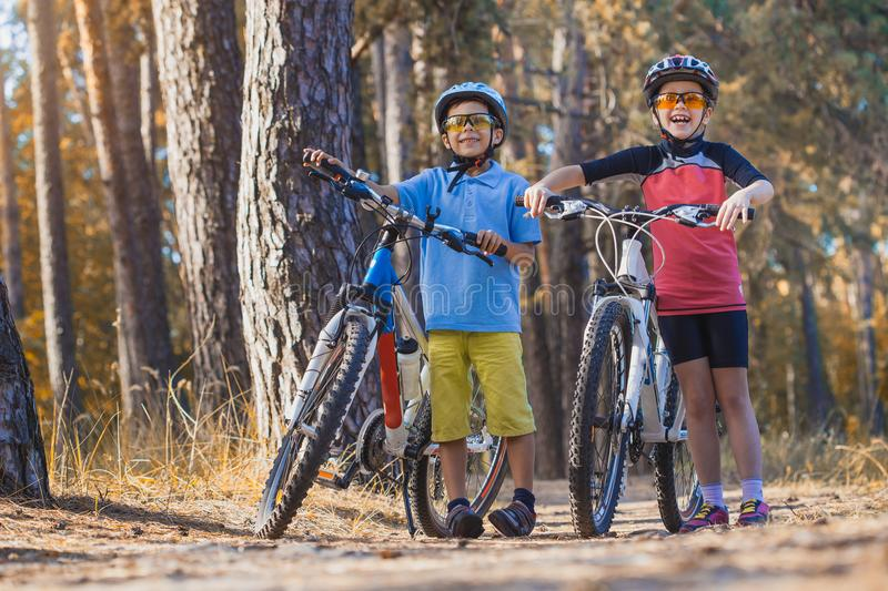Kids on abicycles in the sunny forest. children cycling outdoors in helmet. Kids on abicycles in the sunny forest.happy children cycling outdoors in helmet stock image