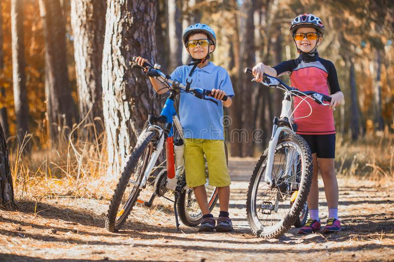 Kids on abicycles in the sunny forest. children cycling outdoors in helmet. Kids on abicycles in the sunny forest.happy children cycling outdoors in helmet royalty free stock images