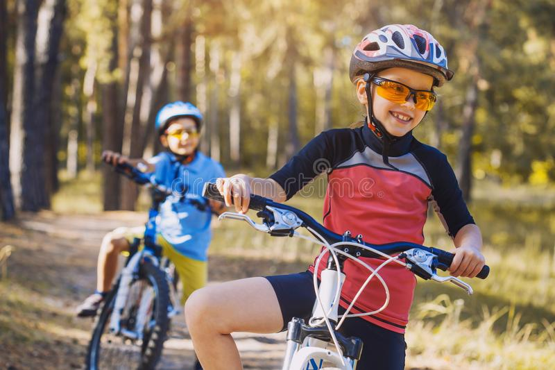 Kids on abicycles in the sunny forest. children cycling outdoors in helmet. Kids on abicycles in the sunny forest.happy children cycling outdoors in helmet stock images