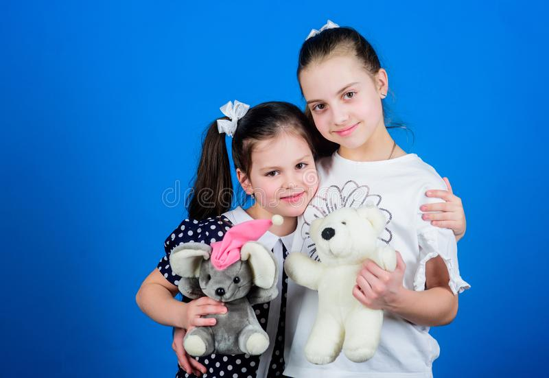 Kids adorable cute girls play with soft toys. Happy childhood. Child care. Sisters or best friends play. Sweet childhood. Childhood concept. Preparing for life royalty free stock photography