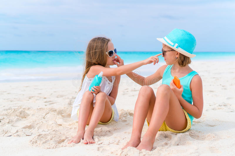 Kids applying sun cream to each other on the beach. The concept of protection from ultraviolet radiation. Sister applying sun cream to sister nose on the beach stock photo
