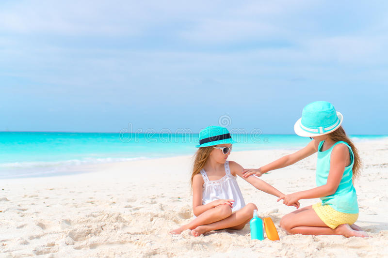 Kids applying sun cream to each other on the beach. The concept of protection from ultraviolet radiation. Sister applying sun cream to sister nose on the beach royalty free stock photo