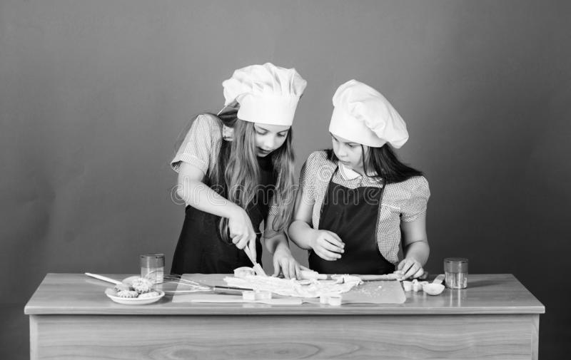 Kids aprons and chef hats cooking. Family recipe. Culinary education. Mothers day. Baking ginger cookies. Girls sisters. Having fun ginger dough. Homemade stock images