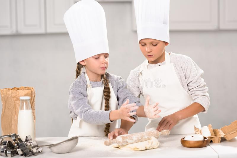 Kids in aprons and chef hats making dough with rolling pin at table. In kitchen royalty free stock image