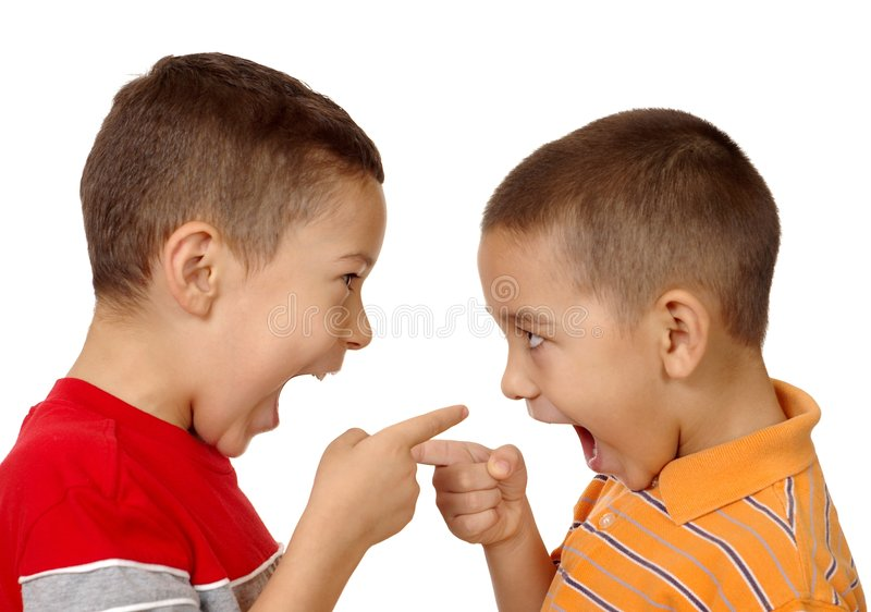 Kids arguing, 5 and 6 years old. Two boys, aged 5 and 6 years, having an argument and pointing fingers at each other, isolated on white background stock photo